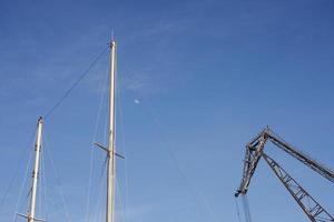 mastros de barco e um guindaste contra um céu azul com a lua foto