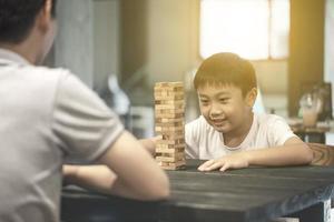 pai e filho jogando jogo de blocos de madeira