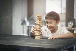 menino jogando um jogo de blocos de madeira