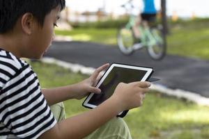 menino usando um tablet do lado de fora