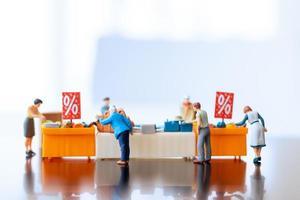 compradores em miniatura com uma bandeja de descontos para comprar itens com desconto