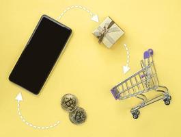 smartphone e moeda de bitcoin de dinheiro virtual dourado em uma mesa com mini carrinho de compras. conceito de pagamento bitcoin, compra ou compra e criptomoeda aceito foto