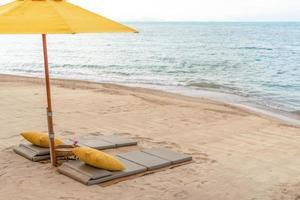 guarda-chuva e cadeira em um fundo de praia tropical de verão com espaço de cópia céu azul