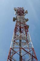 torre de telecomunicações em um fundo de céu nublado foto