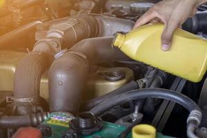 feche um mecânico fazendo serviço e manutenção de automóveis, troca de óleo e filtro de combustível conserto foto