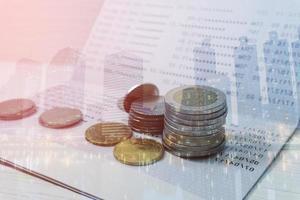 dupla exposição de um plano de fundo da cidade com moedas em um banco de livros de extratos para contabilidade, conceito de banco financeiro