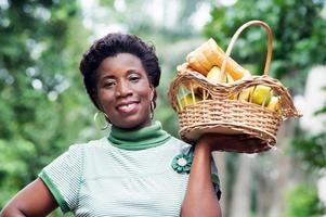 jovem segurando uma cesta de frutas na mão e indo fazer um piquenique