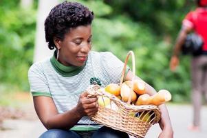 jovem agachada segurando na coxa uma cesta de comida e sorrindo