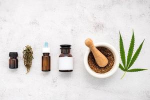 garrafa de vidro de óleo de cânhamo com um almofariz branco e folhas de cânhamo colocadas sobre um fundo de concreto, conceito de aromaterapia