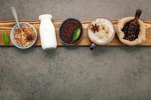 grãos de café torrados com café em pó e ingredientes saborosos para fazer café em um fundo de pedra escura