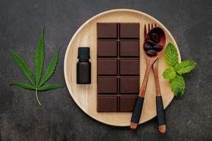 folha de cannabis com chocolate amargo, folhas de plantas e utensílios de madeira em um fundo escuro de concreto foto