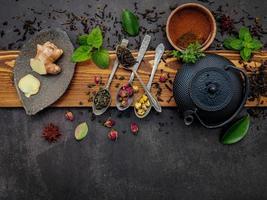 bule de chá preto de ferro fundido com chá de ervas em um fundo de pedra escura