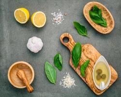 ingredientes para molho pesto caseiro de manjericão, queijo parmesão, alho, azeite, limão e sal do Himalaia sobre um fundo de concreto escuro