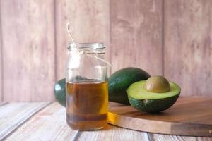 óleo de abacate em fundo de madeira foto