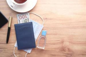 passaporte, dinheiro e desinfetante para as mãos na mesa foto