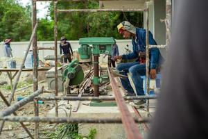 Ratchaburi, Tailândia 2019 - trabalhadores usam uma furadeira elétrica para fazer um furo na viga angular de aço