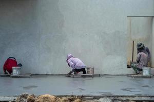 retrato de trás de um grupo de trabalhadores usando espátulas para pavimentar a superfície de cimento foto