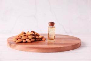 óleo de amêndoa em garrafa na tábua de cortar na mesa foto