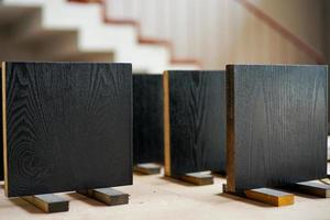 closeup grupo de placas de madeira pretas em formato quadrado no suporte