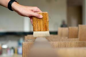 foco seletivo na mão de um carpinteiro segurando um pincel de madeira foto