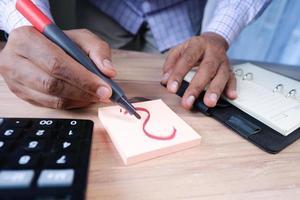mão desenhando um ponto de interrogação no papel na mesa do escritório foto