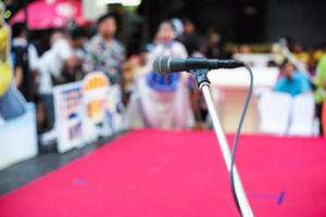 foco seletivo no microfone no palco com multidão turva de pessoas no fundo