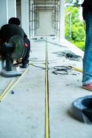 trabalhadores instalando o fio elétrico e a tubulação na casa em construção