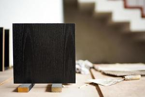 closeup placa de madeira preta em formato quadrado no suporte