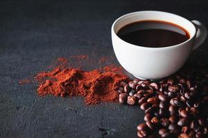 xícara de café com grãos e café moído foto