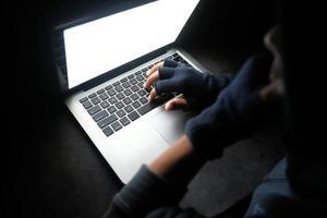 mão digitando no teclado do computador no escuro foto