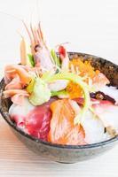tigela de arroz japonês com sashimi de frutos do mar por cima foto