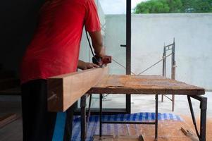 closeup mão de carpinteiro segurando ferramenta elétrica esfregando a superfície da madeira