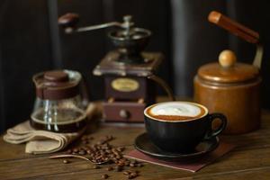 closeup vista superior de xícara de cappucino quente com foco seletivo em grãos de café na mesa de madeira com fundo desfocado do moedor