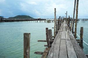 casa de pescador nativo e tradicional fazenda de pesca na costa do mar com antiga passarela de madeira foto