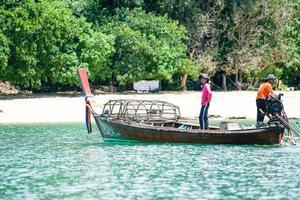 Ko Lanta, Krabi, Tailândia 2019 - pescadores dirigem o barco tradicional de cauda longa e encontram peixes por meio de ferramentas em um dia ensolarado com uma ilha desfocada ao fundo