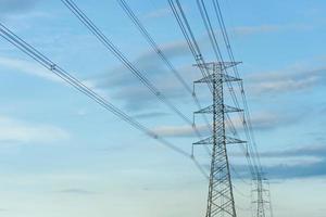 vista de baixo ângulo da torre de alta tensão com cabo elétrico para distribuição e fundo de céu azul
