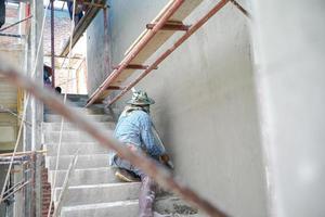 grupo de trabalhadores fica em cima do andaime de aço e constrói parede de cimento gesso na casa em construção