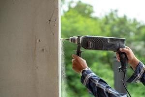 closeup mãos de trabalhador segura uma furadeira elétrica e perfura a parede de cimento