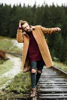 homem barbudo brutal caminha sobre os trilhos nas montanhas dos Cárpatos, ao fundo, altos abetos