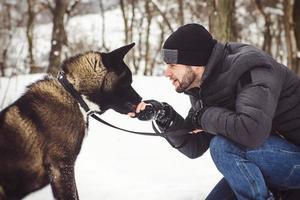 um homem com uma jaqueta e um chapéu de malha caminhando com um cachorro akita americano