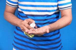 homem usando gel desinfetante contra fundo azul foto
