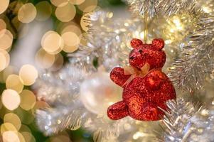 fundo abstrato de luzes brilhantes de bokeh com enfeite desfocado na árvore de Natal prateada em primeiro plano