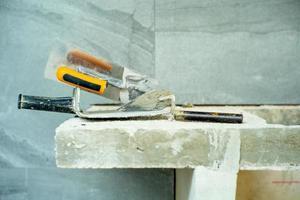 imagem aproximada de uma espátula suja para aplicar a textura de cimento na superfície da parede