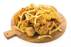 batatas fritas e frango frito no prato de madeira