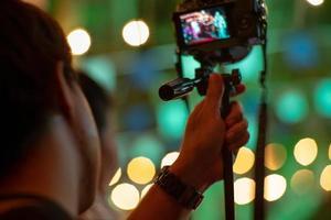 homem em movimento borrado usando a câmera com tripé e luzes cintilantes de bokeh no fundo