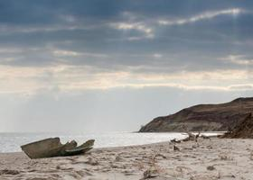 paisagem marítima com um barco quebrado foto