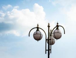 poste de luz contra um céu azul e nuvens brancas foto