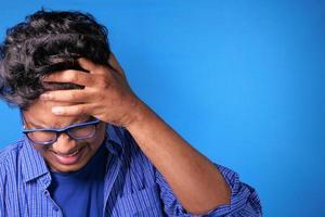 homem segurando a cabeça com a mão sobre fundo azul foto