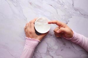 pessoa usando creme de beleza branco foto