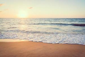 pôr do sol com mar e praia foto